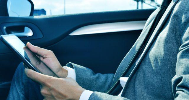 Mężczyzna używający tableta w samochodzie, Fot. Shutterstock.com