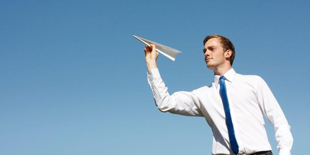 Mężczyzna z papierowym samolotem. Fot. Shutterstock